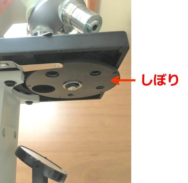 しぼりの写真。観察物を乗せる台(ステージ)の下にある円盤に、大きさの違う5つの穴がついている。