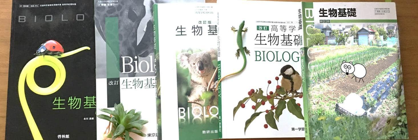 生物基礎の教科書5冊が並び、その周りに、魚、ヒト、ナメクジ、カエルの模型が置いてある写真。
